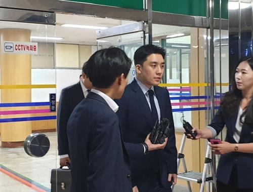 8月28日晚上,勝利(右二)在首爾地方警察廳智慧犯罪偵查隊接受調查後走出大樓。 韓聯社