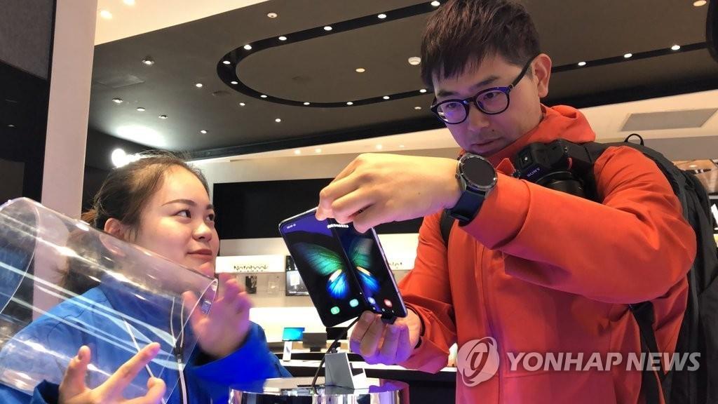 資料圖片:11月8日,在上海南京東路三星旗艦店,一名顧客在試用三星折疊屏手機Galaxy Fold。 韓聯社