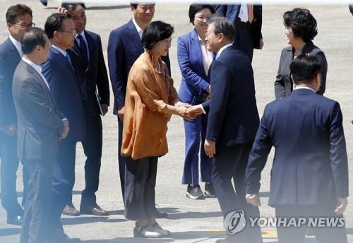 資料圖片:2018年7月8日,在京畿道城南市首爾機場,文在寅在出訪前與時任共同民主黨黨首秋美愛握手。 韓聯社