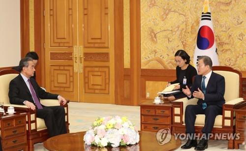 12月5日下午,在青瓦臺,南韓總統文在寅(右)會見到訪的中國國務委員兼外交部長王毅。 韓聯社