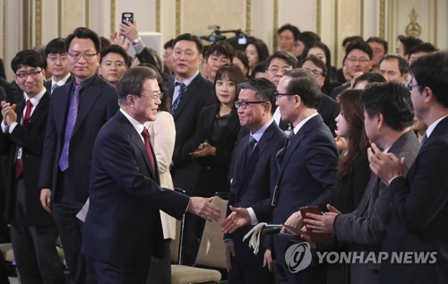 1月14日上午,在青瓦臺迎賓館,南韓總統文在寅舉行新年記者會與在場人士握手致意。 韓聯社