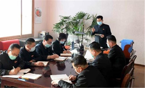 金在龍(中間站立)佩戴口罩主持會議。 韓聯社/《勞動新聞》官網截圖(圖片僅限南韓國內使用,嚴禁轉載複製)