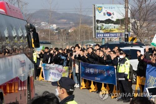 2月15日,在忠清南道牙山市,當地居民為乘車離開警察人才開發院的回韓人員送行。 韓聯社