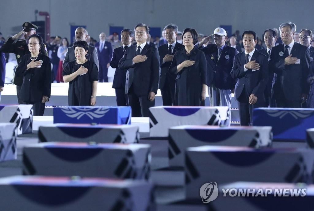 6月25日,在位於京畿道城南市的首爾機場,南韓總統文在寅(居中)和夫人金正淑女士出席南韓戰爭70週年紀念活動並向國旗行禮。 韓聯社