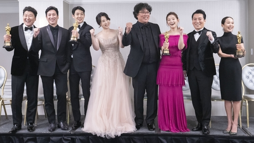 資料圖片:2月10日,《寄生蟲》導演奉俊昊(中)和演員們獲得奧斯卡金獎後合影留念。 韓聯社