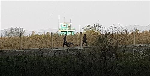 資料圖片:朝鮮士兵在朝中邊境線持槍巡邏,圖片攝于2020年10月。 韓聯社
