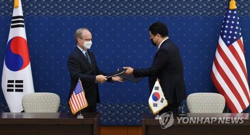 4月8日,在首爾外交部大樓,南韓外交部第一次官崔鐘建(右)和美國駐韓大使館臨時代辦拉普森簽字後互換第11份防衛費分擔特別協定。 韓聯社