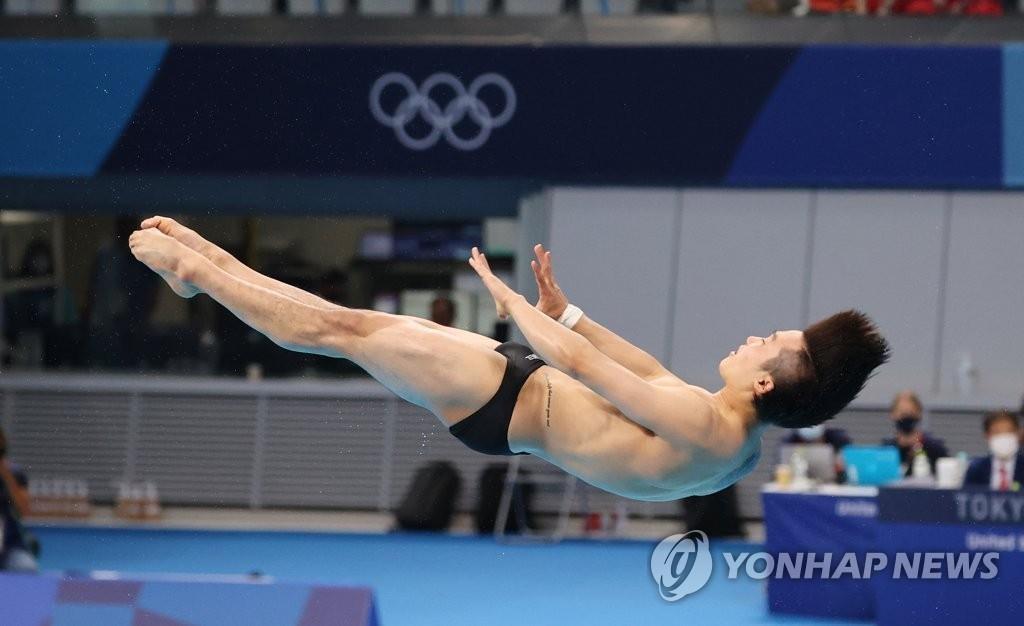 8月3日,在東京水上運動中心進行的東京奧運會男子3米跳板跳水決賽中,南韓選手禹河藍正在翻跳入水。 韓聯社