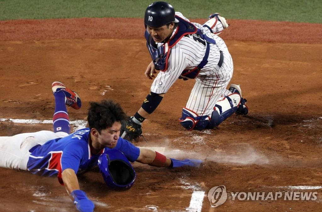 8月4日,在日本橫濱棒球場,南韓隊和日本隊進行東京奧運會棒球準決賽。圖為南韓球員樸海旻借隊友姜白虎打出安打的機會跑回本壘得分。 韓聯社