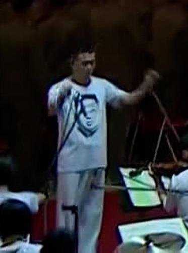 """據朝鮮中央電視臺10月12日報道,在朝鮮勞動黨建黨76週年之際,國防發展展覽會""""自衛-2021""""前一日在三大革命展館開幕。圖為樂團指揮者身穿印有國務委員會委員長金正恩頭像的T恤。 韓聯社/朝鮮央視畫面截圖(圖片僅限南韓國內使用,嚴禁轉載複製)"""