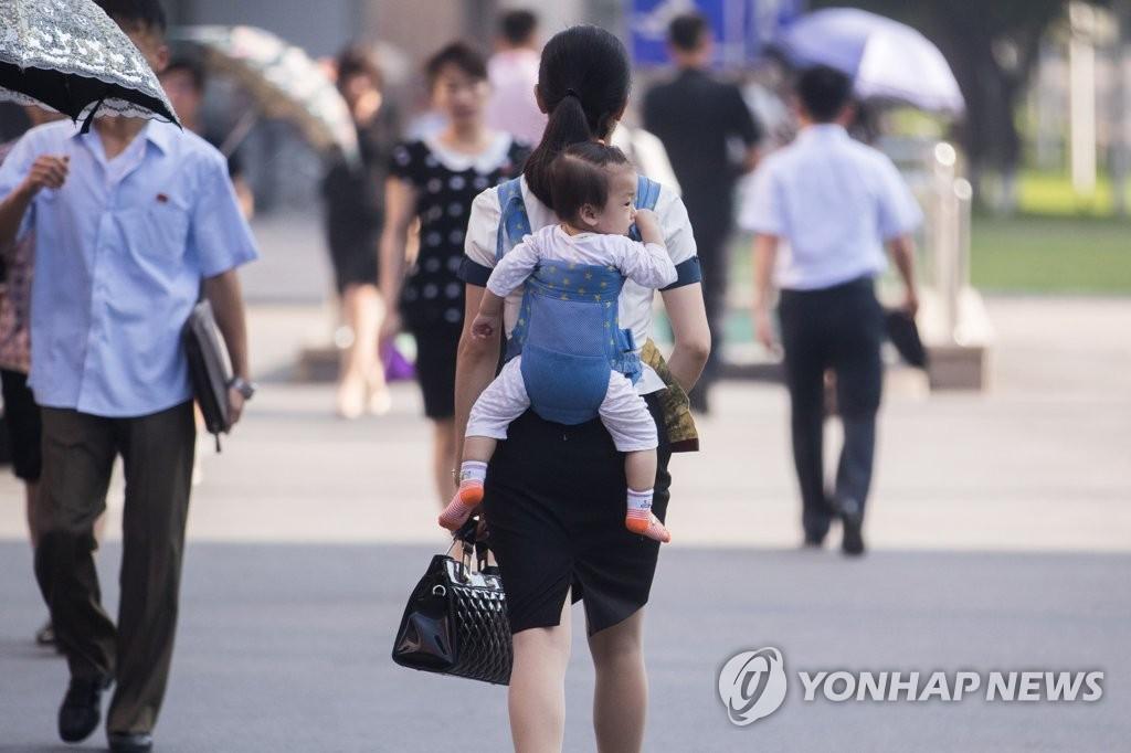 資料圖片:2018年7月4日上午,在平壤街頭,一位身著西裝的女士背著孩子走在街頭。 韓聯社/韓媒攝影記者團供圖(圖片嚴禁轉載複製)