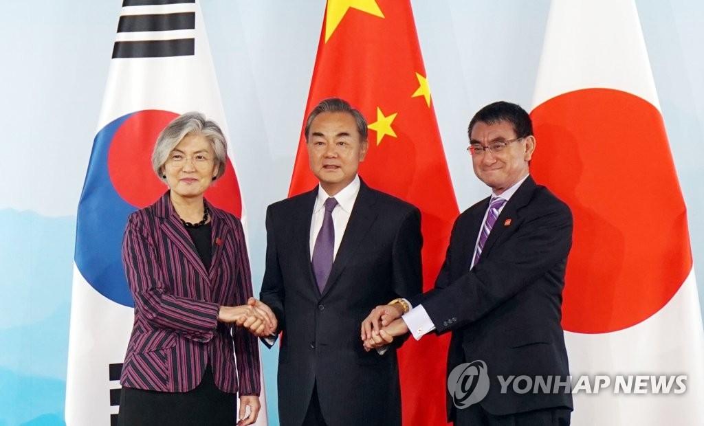 8月21日,在北京,韓中日外長握手合影。 韓聯社/聯合採訪團