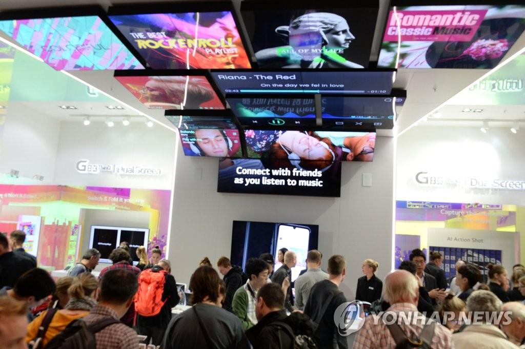 """資料圖片:當地時間9月8日,在德國柏林國際電子消費品展覽會(IFA)上,訪客們在LG電子展臺欣賞""""V50S ThinQ""""和雙屏新品。 韓聯社/LG電子供圖(圖片嚴禁轉載複製)"""