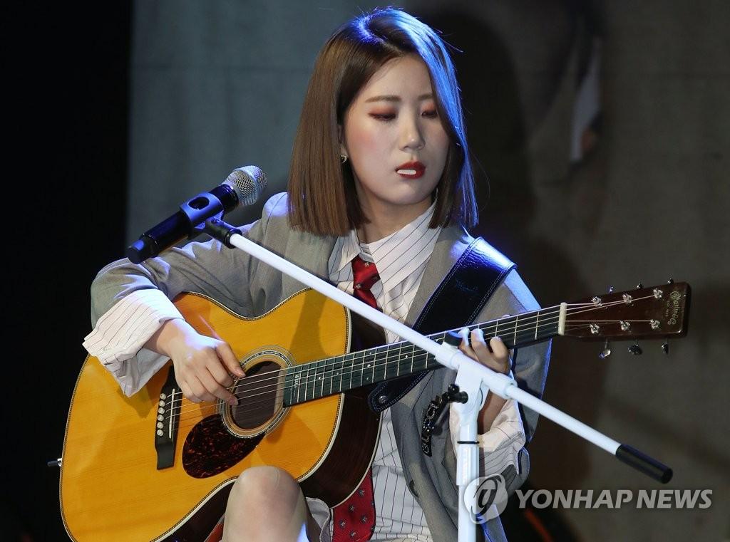 9月10日下午,在首爾,禹智潤抱著吉他銜著撥片伴奏《工作狂》。 韓聯社