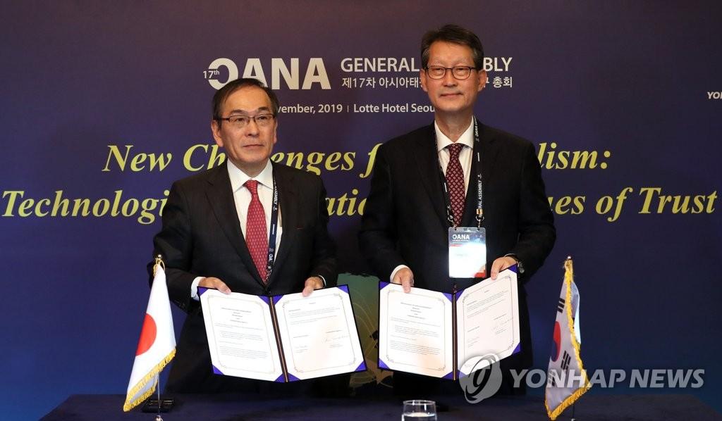 11月8日,在首爾樂天酒店舉行的第十七屆亞通組織大會上,南韓聯合通訊社社長趙成富(右)與日本共同社社長水谷亨簽署關於加強合作的諒解備忘錄後合影留念。 韓聯社