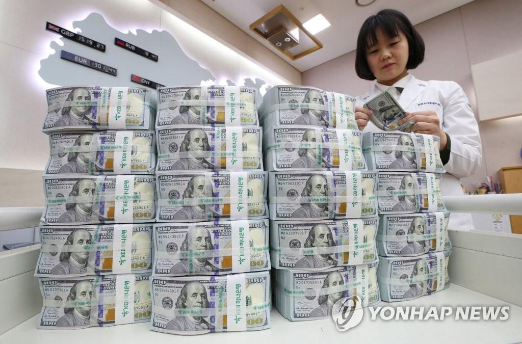 資料圖片:2019年12月4日,在首爾中區KEB韓亞銀行總行,一名職員正在點鈔。 韓聯社