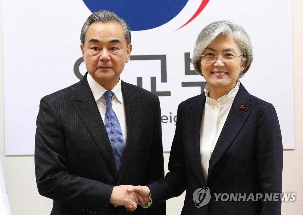 12月4日,在首爾市鐘路區的南韓外交部,康京和(右)與王毅握手合影。 韓聯社