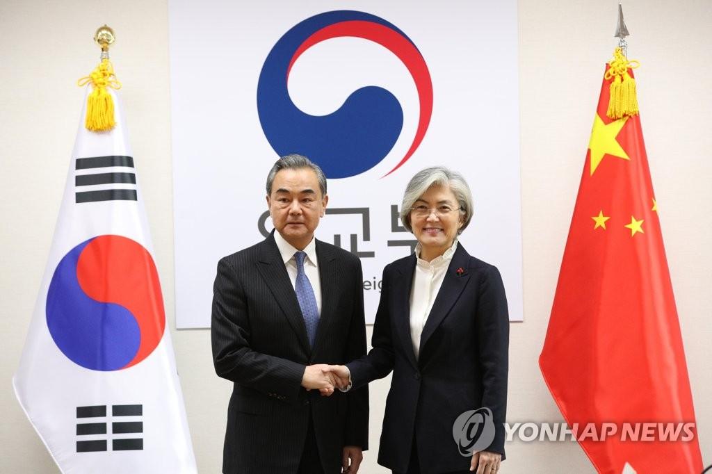 12月4日,在位於首爾的南韓外交部大樓,南韓外交部長官康京和(右)與到訪的中國國務委員兼外交部長王毅握手合影。 韓聯社