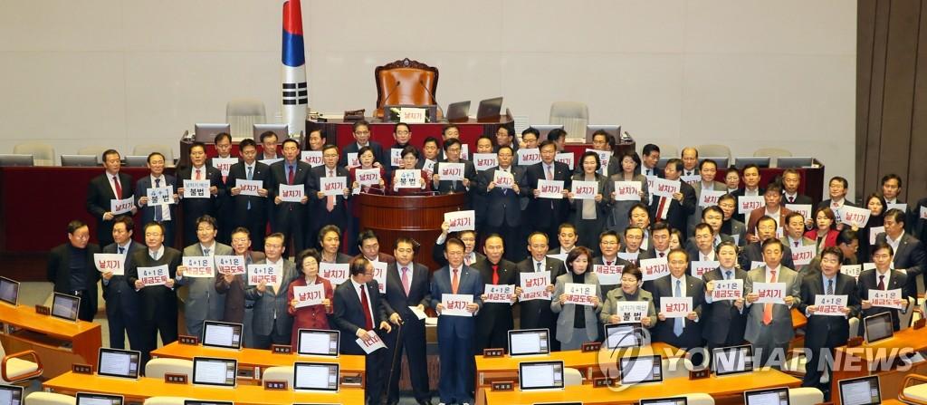 資料圖片:12月10日,自由南韓黨議員手舉牌子,對明年度預算案獲得通過表示抗議。 韓聯社
