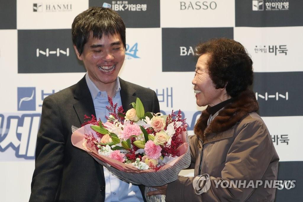 資料圖片:12月21日,李世石(左)接過母親送的花束。 韓聯社