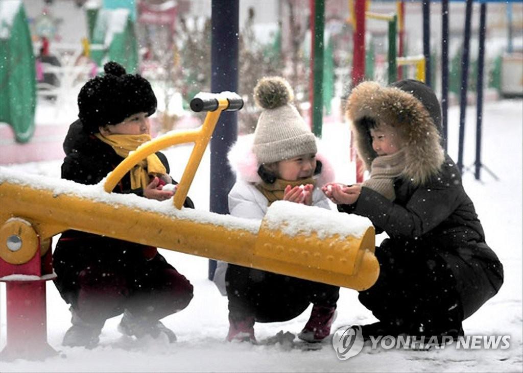 資料圖片:玩雪的朝鮮兒童 韓聯社/《勞動新聞》朝中社(圖片僅限南韓國內使用,嚴禁轉載複製)