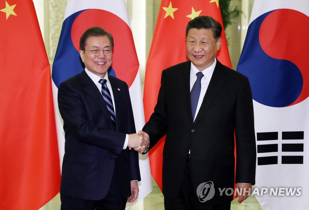 2019年12月23日,在北京人民大會堂,南韓總統文在寅(左)與中國國家主席習近平握手合影。 韓聯社