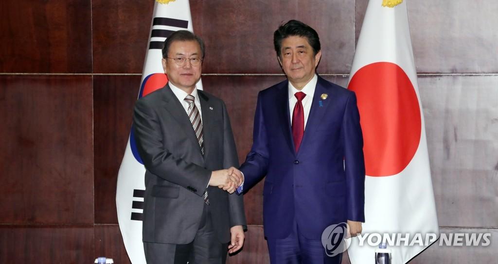 資料圖片:12月24日,在成都香格里拉酒店,南韓總統文在寅(左)和日本首相安倍晉三在會談開始前握手合影。 韓聯社