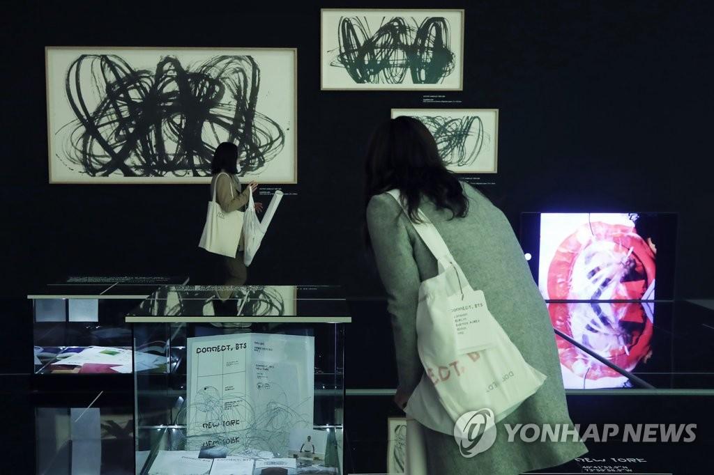 """資料圖片:1月28日下午,南韓男團防彈少年團(BTS)攜手現代美術巨匠進行的美術展示活動""""CONNECT,BTS""""在首爾東大門設計廣場開幕,一名訪客前來觀看展覽。 韓聯社"""