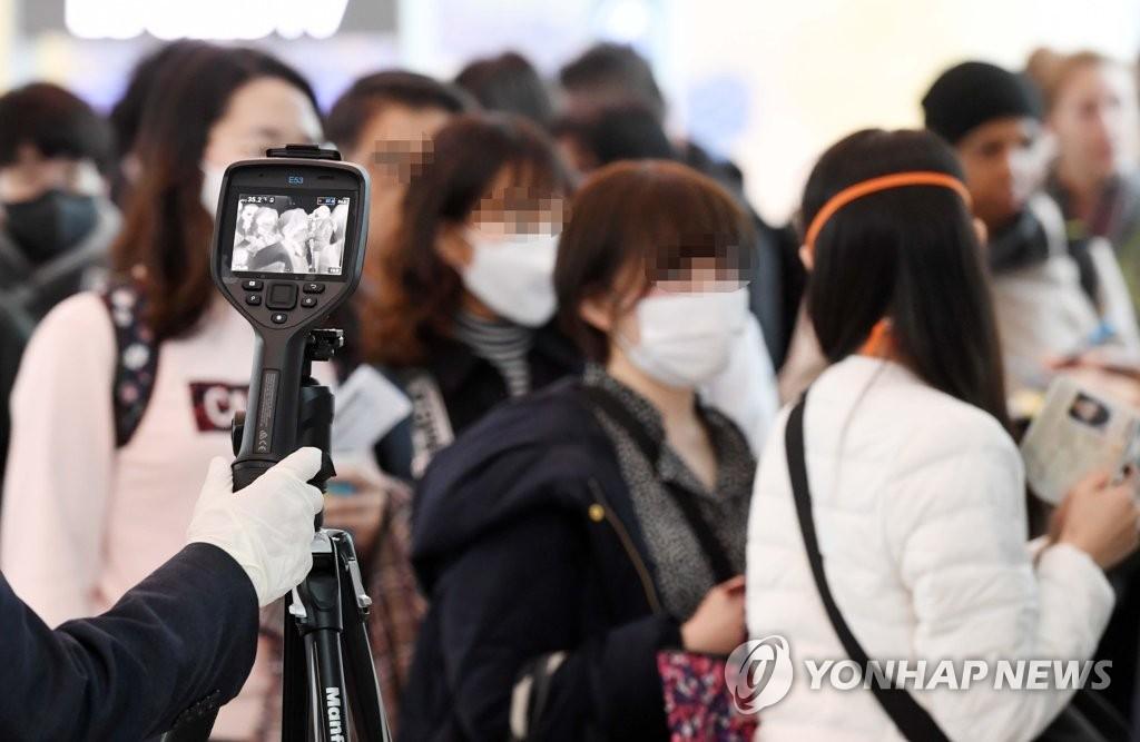 資料圖片:2月28日,在仁川國際機場洛杉磯航班登機口,大韓航空工作人員篩查發熱旅客。 韓聯社