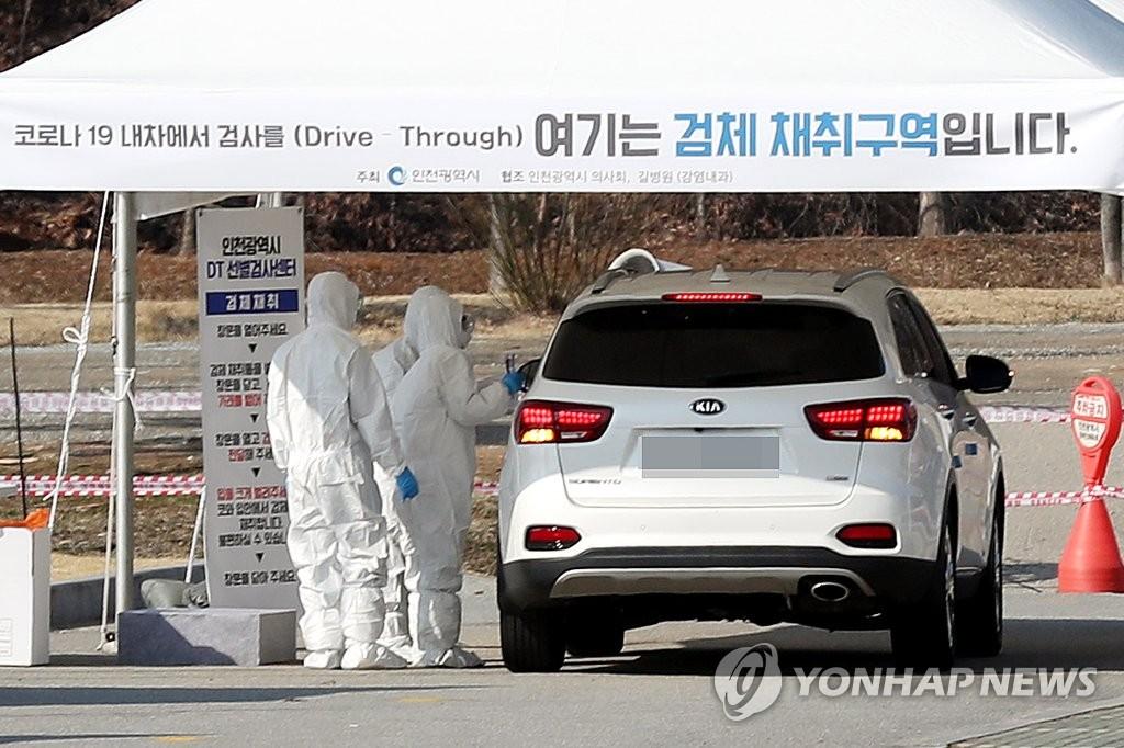 """資料圖片:3月2日,在設于仁川市延壽區的""""免下車""""篩查診所,一名市民在車內接受新冠病毒(COVID-19)檢測。 韓聯社"""