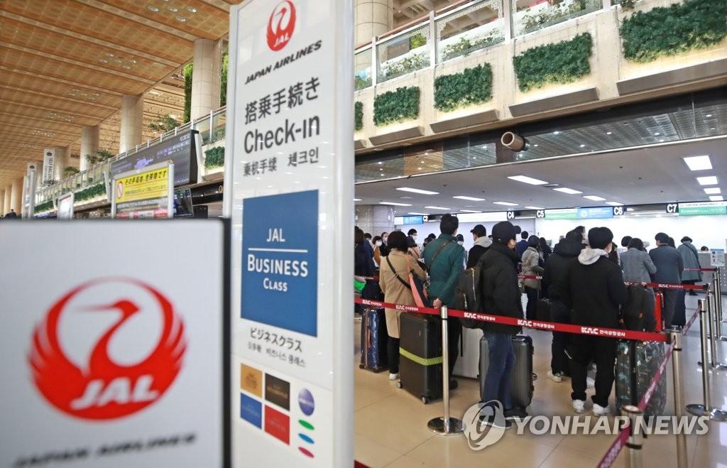 資料圖片:3月8日,在首爾金浦機場,準備前往日本的乘客排起長龍等待辦理乘機手續。 韓聯社