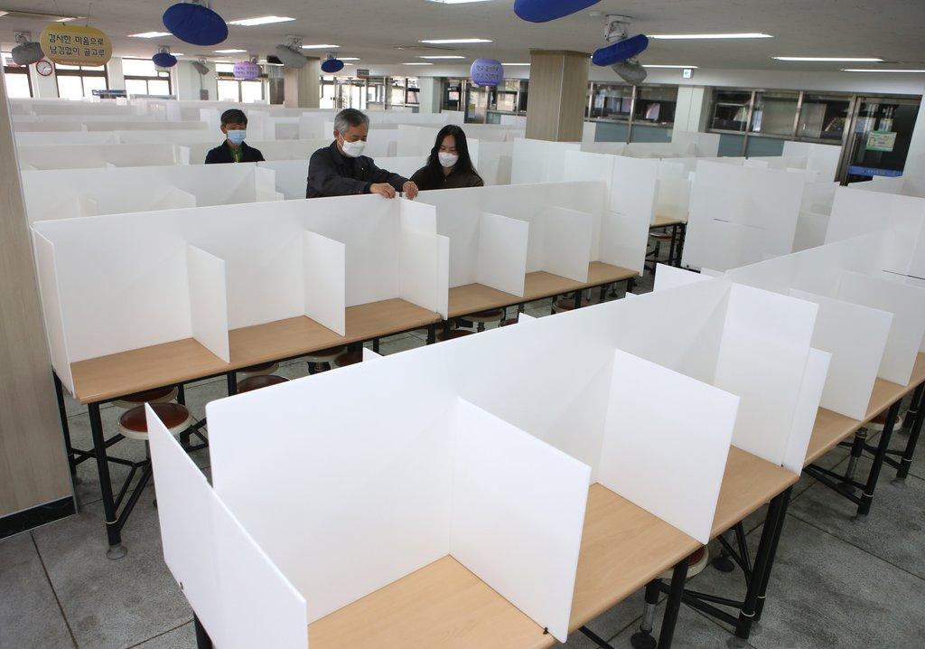 資料圖片:3月31日,在大邱市的慶北高中食堂,餐桌上裝起隔斷板以防新冠病毒感染。 韓聯社
