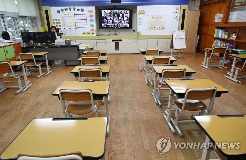 資料圖片:4月20日,在首爾龍山區龍山小學一年級教室�堙A老師與學生們線上交流。受新型冠狀病毒(COVID-19)疫情影響,南韓中小學史上首次線上開學,小學一到三年級當天最後一批加入線上上課的行列。 韓聯社