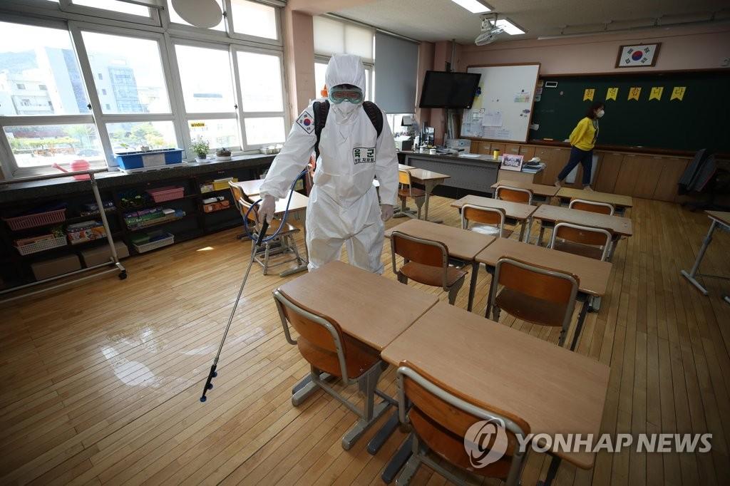 資料圖片:4月21日,在大邱市中區明德小學,一名陸軍士兵為教室消毒。 韓聯社