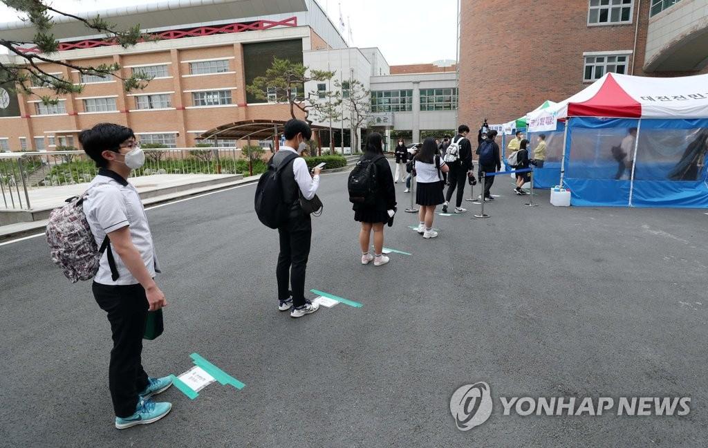 資料圖片:5月20日,在位於大田市儒城區的一所高中,高三的學生們保持距離有序入校。當天,南韓全體高三學生時隔80天返校復課。 韓聯社