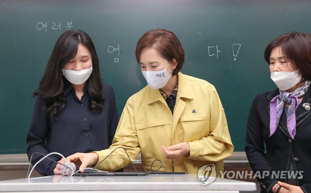 資料圖片:5月25日上午,在首爾龍山區的一所中學,南韓副總理兼教育部長官俞銀惠(中)與教師們交談。在初中生、小學生等也即將返校復課之際,俞銀惠視察該校,檢查防疫工作。 韓聯社