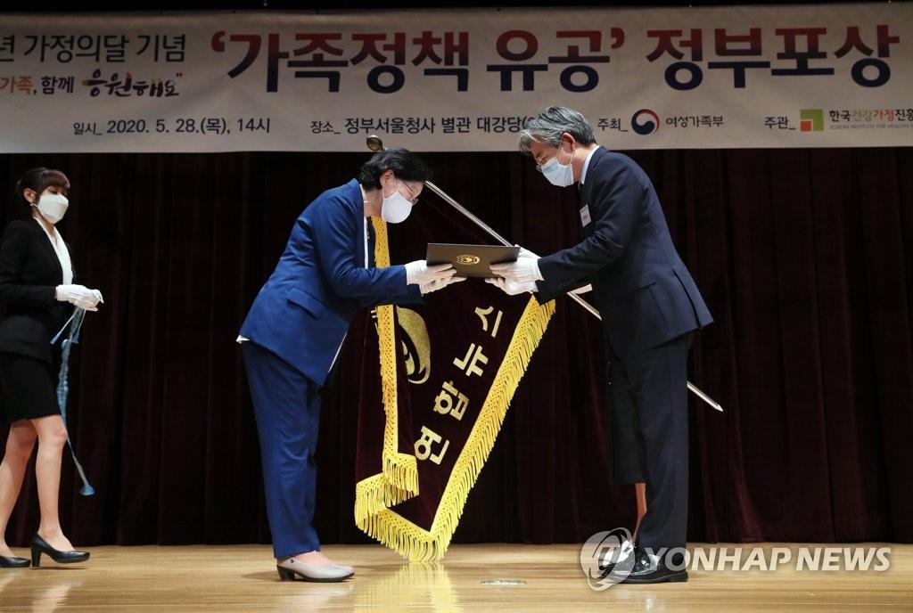 5月28日,女性家庭部長官李貞玉(左)向韓聯社韓民族中心本部長樸相鉉(音)頒發國務總理表彰獎。 韓聯社