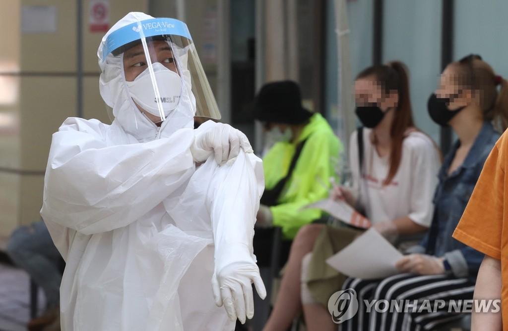 資料圖片:醫療人員穿著防護服準備進行病毒檢測。 韓聯社