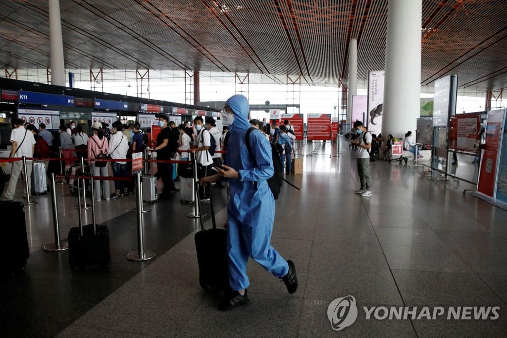 資料圖片:6月17日,一名旅客穿著防護服走在北京首都機場國際出發候機廳。 韓聯社/路透社(圖片嚴禁轉載複製)