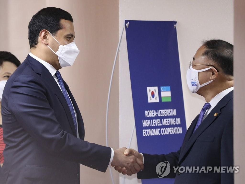 7月7日下午,在中央政府首爾辦公樓,洪楠基(右)和烏穆爾扎科舉行會談前握手致意。 韓聯社