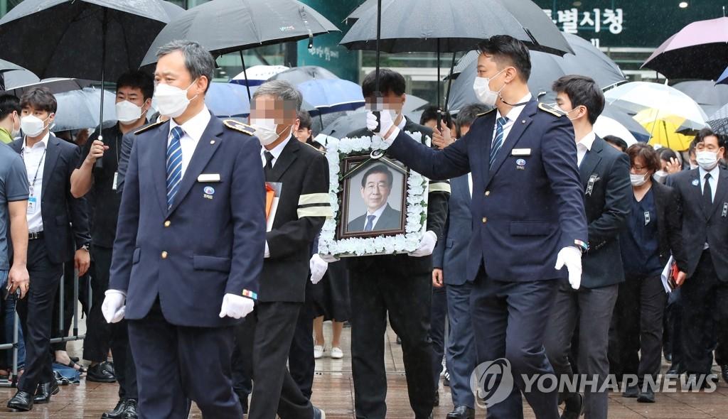 7月13日上午,首爾市政廳,樸元淳的遺屬捧著遺像到達遺體告別儀式現場。 韓聯社