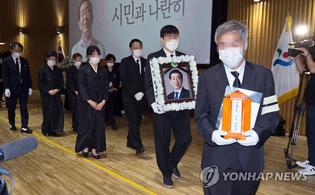 7月13日上午,在首爾市政廳多功能廳,遺屬捧著樸元淳的靈牌和遺像退場。 韓聯社/攝影記者團供圖(圖片嚴禁轉載複製)