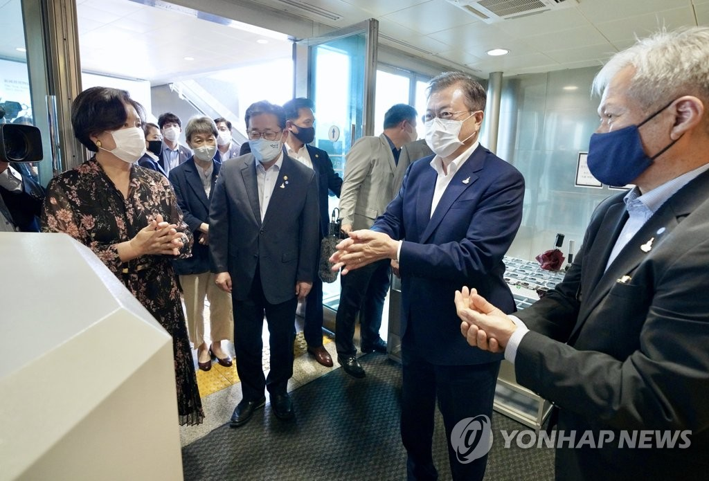 7月30日,南韓總統文在寅(右二)攜夫人金正淑女士(左)前往國立中央博物館觀看大型國寶展覽。圖為文在寅一行在入口處進行常規手部消毒。 韓聯社