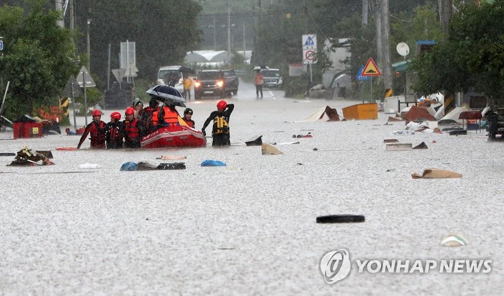 資料圖片:8月5日上午,江原道鐵原郡金化邑一帶被水淹沒,消防人員用橡皮艇營救當地居民。 韓聯社