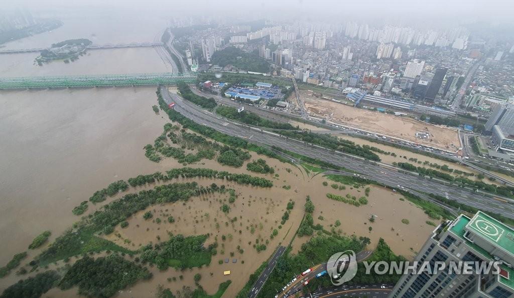 資料圖片:8月6日,受暴雨影響,漢江鐵橋附近的路面被江水淹沒。 韓聯社
