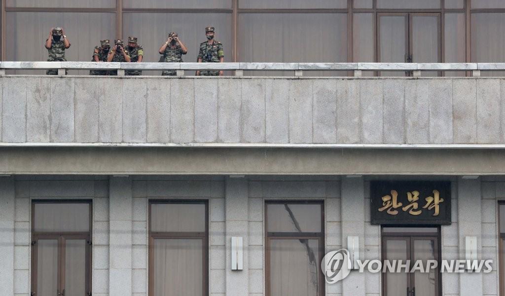 """資料圖片:9月16日,在韓朝邊境板門店朝方一側的""""板門閣"""",朝鮮軍人手持望遠鏡向韓方一側觀望。 韓聯社/聯合攝影團"""