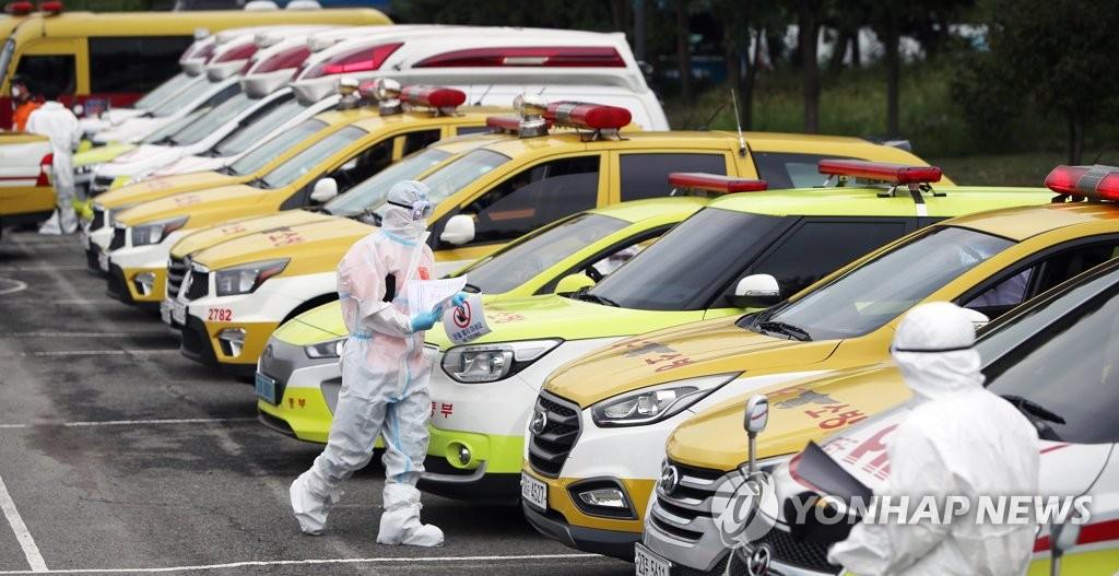 資料圖片:9月16日下午,在大邱市達西區,消防隊員演練移送大批新冠病人。 韓聯社