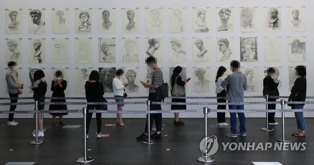 資料圖片:10月4日,在位於首爾三清洞的國立現代美術館,訪客們保持距離排隊等候入場。 韓聯社