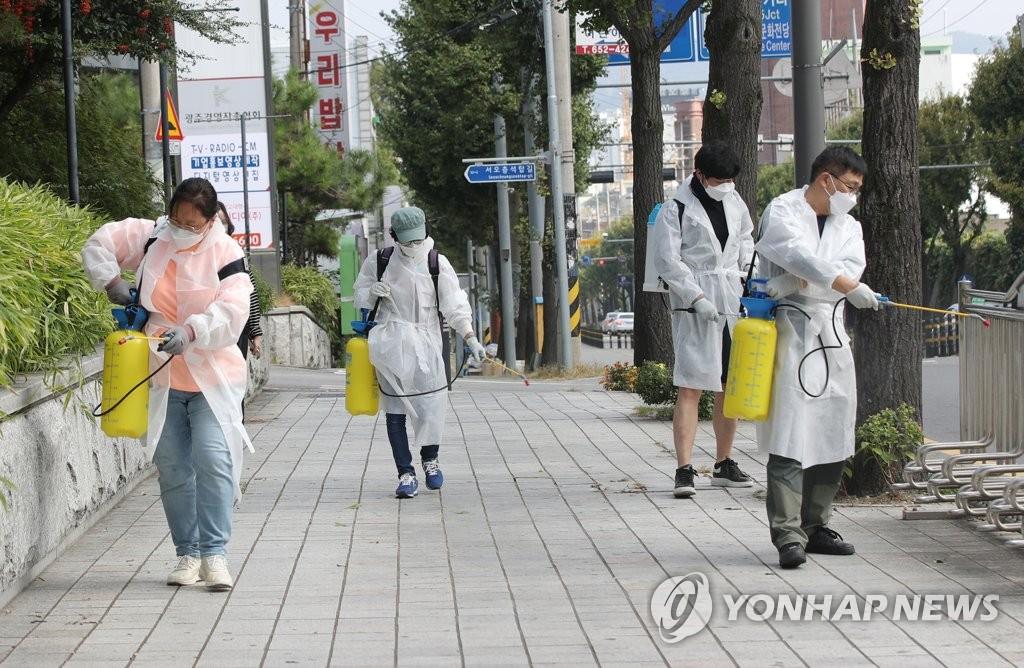 資料圖片:10月12日,在光州市南區社稷洞一帶,工作人員在街頭消毒防疫,防範新冠疫情擴散。 韓聯社