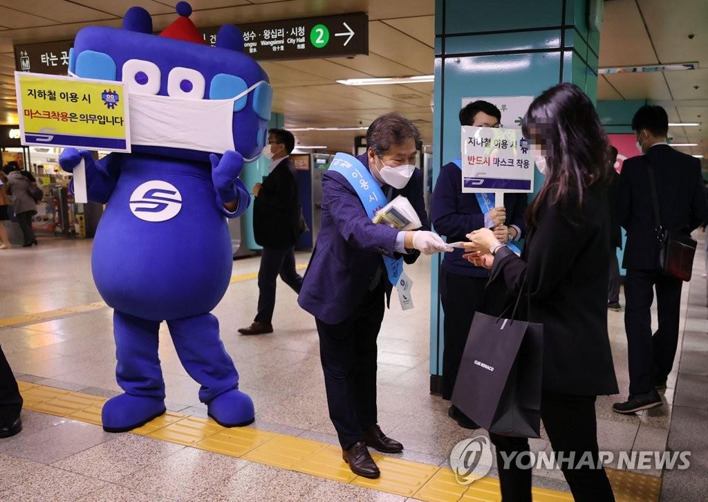 資料圖片:10月13日,在首爾蠶室地鐵站,首爾交通公社工作人員給市民分發口罩。南韓當天起要求民眾在利用公共交通工具和訪問醫療機構時必須佩戴口罩,違規者從下月13日起將被處以10萬韓元(約合人民幣600元)的罰款。 韓聯社